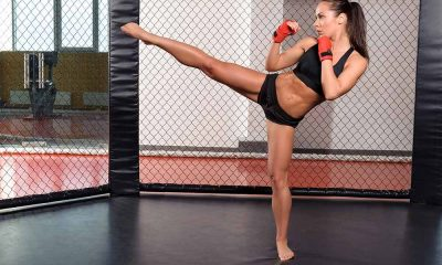 Female martial artist doing a high kick in an mma cage